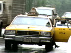 businessman getting into yellow cab ZO to intersection cars stop at light pan with bunch of cabs passing in FG