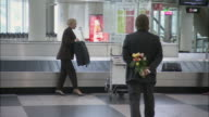 MS ZI Businessman giving bouquet of flowers to businesswoman near baggage claim carousel / Munich, Germany