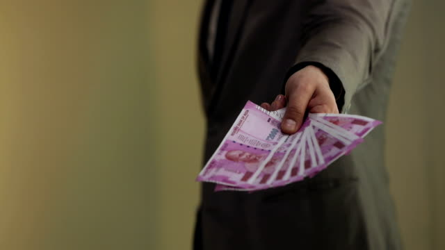 Businessman giving indian two thousand banknotes, Delhi, India