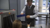 MS Businessman going through airport security checkpoint/ MS Security worker looking at x-ray screen/ ZI CU X-ray screen & console/ Munich, Germany