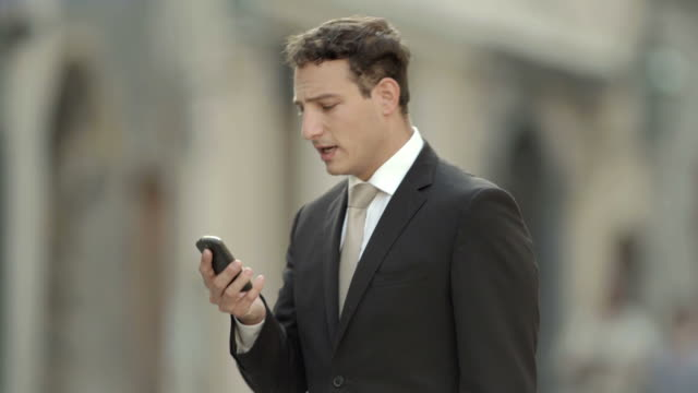 HD: Businessman Having Video Call On A Street