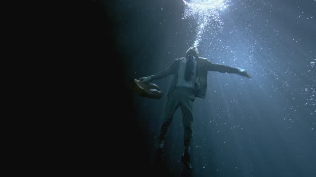 WS SLO MO Businessman holding briefcase treading underwater / London, United Kingdom