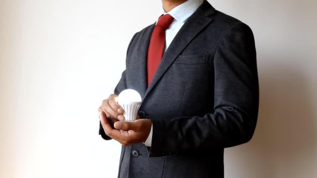 Businessman holding bulb light