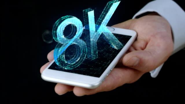 Geschäftsmann hält Handy mit 3D Hologramm von 8K