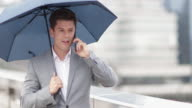 Businessman in city holding umbrella talking on smartphone
