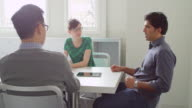 MS Businessman in discussion with colleagues during team meeting in small conference room