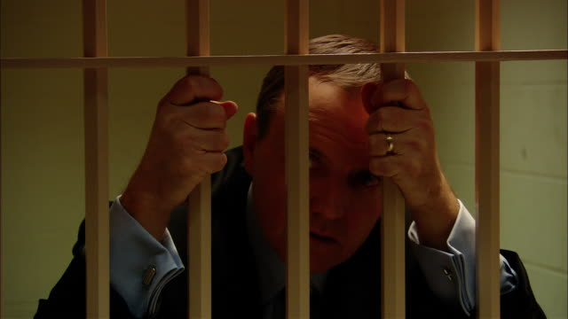 CU TU Businessman in jail cell gripping bars/ New Jersey
