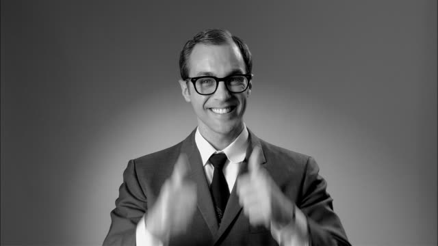 B/W MS Businessman in suit and glasses giving thumbs up and OK sign/ New York City