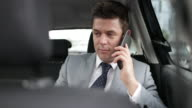 Businessman in taxi cab using smartphone
