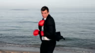 Businessman is boxing at the seaside