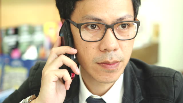 HD : Businessman is using smart phone at work place