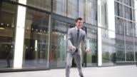 Businessman leaving work doing a heal click jump
