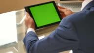 Businessman look at Digitial Tablet Green screen