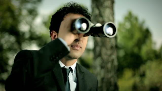 Zakenman op zoek weg met verrekijker in de natuur.