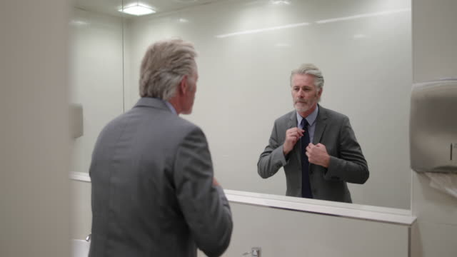 Businessman looking in a mirror preparing for business meeting