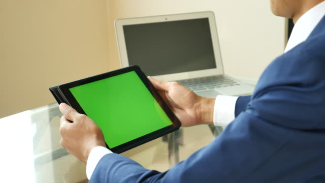Businessman looking on Digital tablet with Green screen