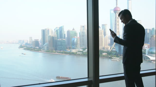 WS businessman looking out a window at Shanghai skyline
