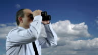 Businessman Looking Through a Binoculars with Moving Clouds