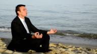 businessman meditating on the beach. (vetta)