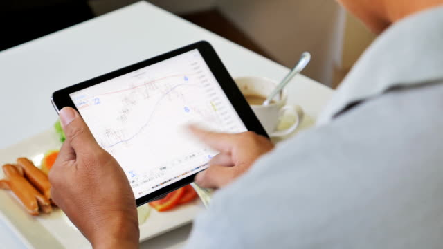 Businessman nalyzing market data information on a digital tablet