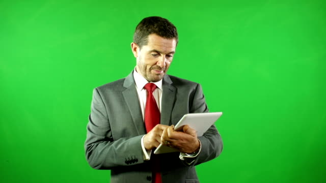 Businessman on Digital Tablet in front of Green Screen