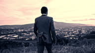 Businessman on the hill above the city