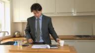 MS PAN Businessman opening letter in kitchen / Hackney, United Kingdom