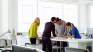 MS businessman presenting project to coworkers at office workstation