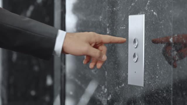 """SLO, MO, DS Geschäftsmann, drücken die Schaltfläche """"Aufzug"""