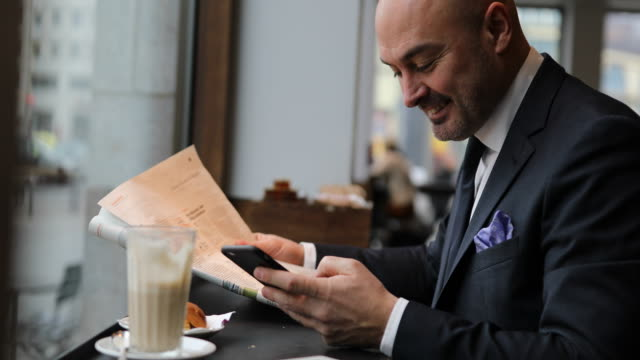 Businessman reading newspaper and texting in cafe