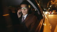 Businessman riding in the back seat of car, talking on the phone and smiling.