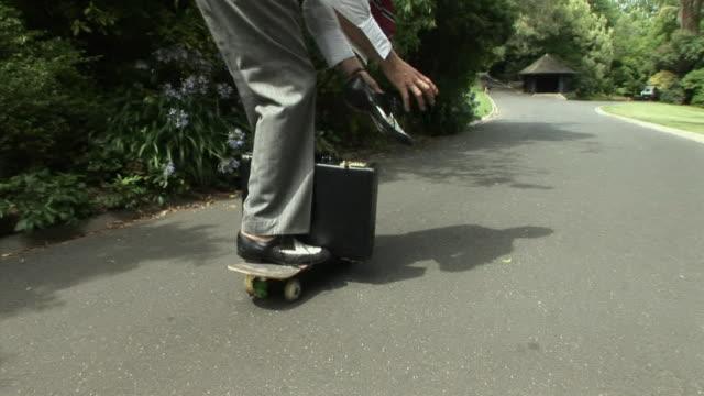 MS, Businessman riding skateboard in park, low section, Melbourne, Victoria, Australia