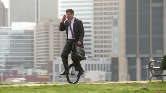 WS PAN Businessman riding through park and talking on mobile phone while riding unicycle/ Richmond, Virginia