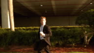 MS PAN SLO MO Businessman running with briefcase and holding cup of coffee, looking back over shoulder / Miami Beach, Florida, USA