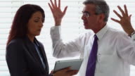 Businessman scolding a businesswoman in an office