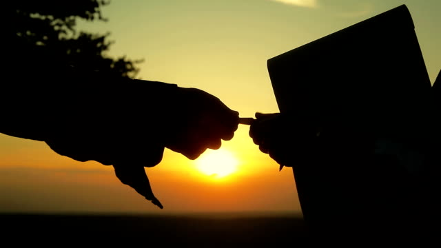 Businessman shakes hands at Sunset on mountain Submit