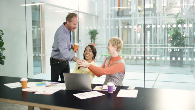 MS TS Businessman shaking hands with colleagues in meeting in office