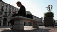 Businessman sits on bench in piazza, talks on phone