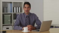 Businessman sitting at desk and talking to camera with laptop