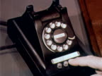 1960 MONTAGE MS businessman sitting at desk / CU man's hand hitting button on phone / MS secretary answering phone / CU woman's hand dialing rotary phone / USA
