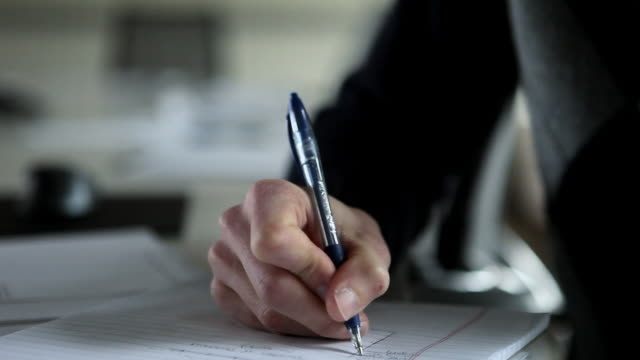 CU Businessman sitting at office conference table writing on notepad/Seattle, Washington, USA