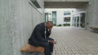 MS DS Businessman sitting in courtyard and text messaging, Squamish, British Columbia, Canada