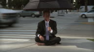 MS Businessman sitting on street corner holding umbrella / South Beach, Florida, USA