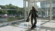 MS DS Businessman skateboarding in lobby / Bangkok, Thailand