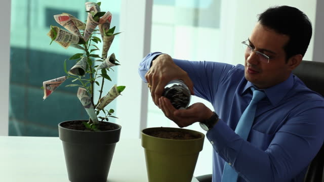 Businessman sowing coins in an office