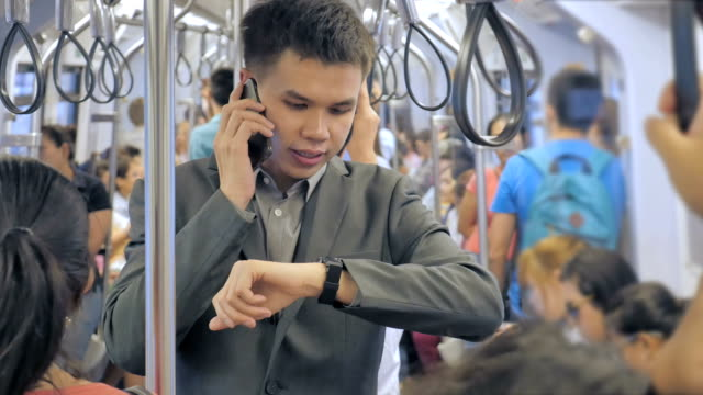 Businessman standing and using smartphone on a train