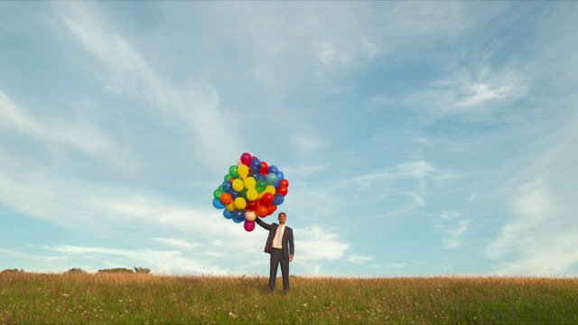 MWS businessman standing  in  field releasing  large bunch of balloons