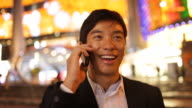 A businessman standing on a brightly lit street cheerfully converses on a cell phone.