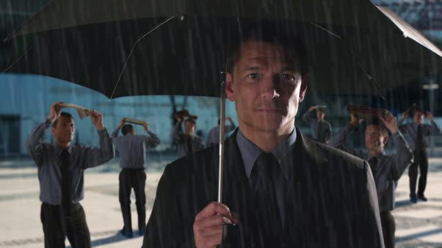Businessman standing under an umbrella in the rain/Marbella region, Spain