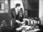 B/W 1929 businessman standing up from desk looking at paper exiting office / newsreel